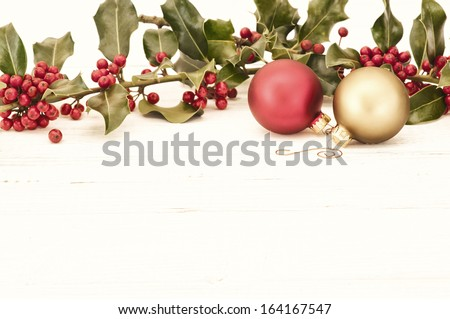 Antique Christmas Holly and Ornaments across the top or above White Wood Boards with background room or space for text, copy, or your words, horizontal with bleach bypass treatment. - stock photo