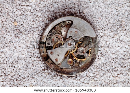 antique clock mechanism buried in sand - stock photo