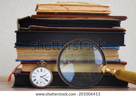 antique clock with loupe  on pile of  vintage books background - stock photo