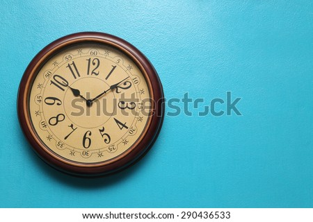Antique clocks vintage retro styles Hanging on the wall of blue, with space for text. - stock photo