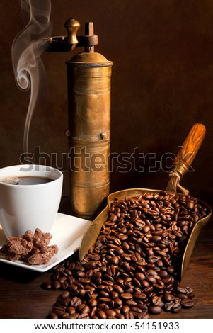 Antique coffee grinder with steaming coffee, cookies and books - stock photo