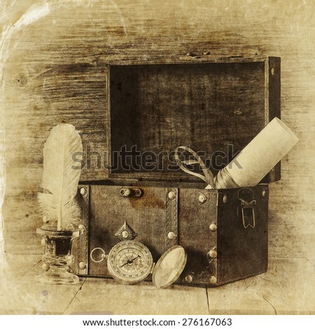Antique compass, inkwell and old wooden chest on wooden table.  black and white style old photo  - stock photo