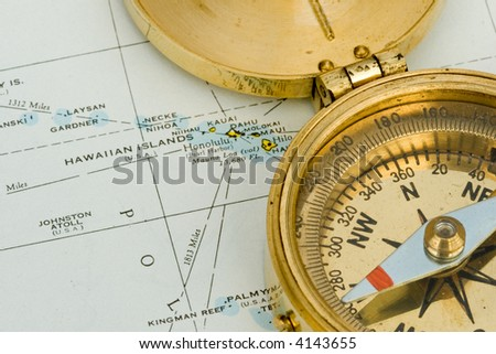 Antique compass used by explorers for finding directions and reading a map or chart - stock photo