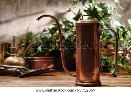 Antique copper watering can and old gardening tools in a retro garden greenhouse - stock photo