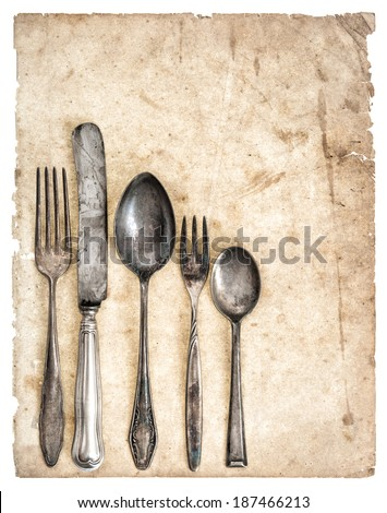 Antique cutlery and old cook book page isolated on white background. Retro kitchen utensils knife, fork and spoons - stock photo