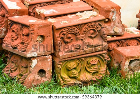 Antique decorative molded bricks salvaged from  demolished building stacked on grass. - stock photo