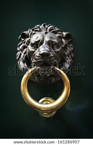 Antique door knob in the form of a lion's head with golden ring in its jaws on old wooden door, Rome, Italy - stock photo