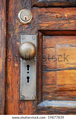 antique door knob on old wooden door with panels - stock photo