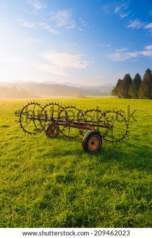 Antique farm implement in a farming landscape, Stowe Vermont, USA - stock photo