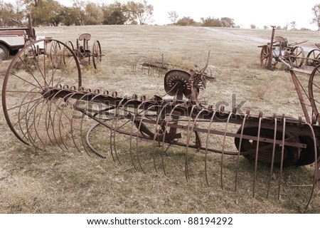 Antique farming equipment left on abandoned fields (done in sepia) - stock photo