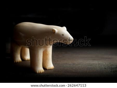 Antique figure of polar bear made of walrus tusk on black background - stock photo