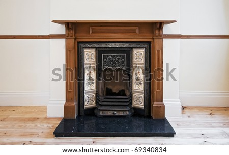 antique fireplace with carved wooden frame and hand painted ceramic tiles - stock photo