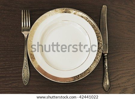 antique fork, knife and plate - stock photo