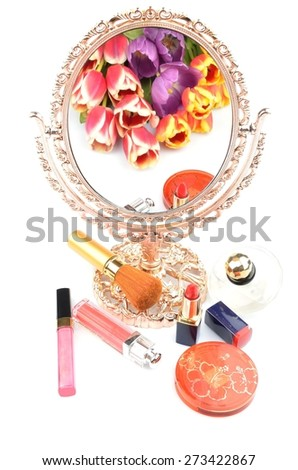 Antique gilded mirror reflecting a bouquet of flowers tulips and women's cosmetics and makeup on a white background - stock photo