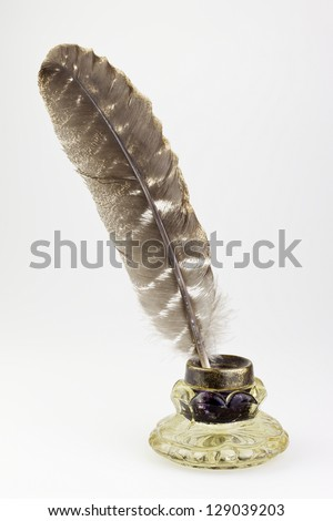 antique glass inkwell and old pen isolated background - stock photo