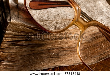 Antique glasses on old weathered book. Close-up view - stock photo
