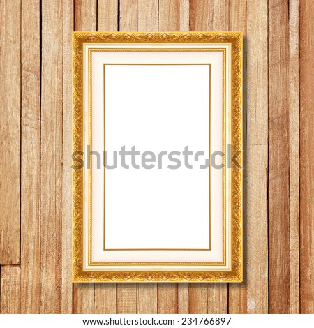 Antique gold frame on wooden wall;. Empty  picture frame on wooden wall. - stock photo