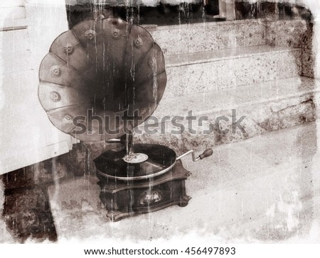 Antique gramophone on the stairs of a house (in black and white, vintage style with special vintage effects) - stock photo
