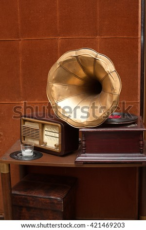 Antique gramophone with golden horn and radio on table on vintage brown wall background - stock photo