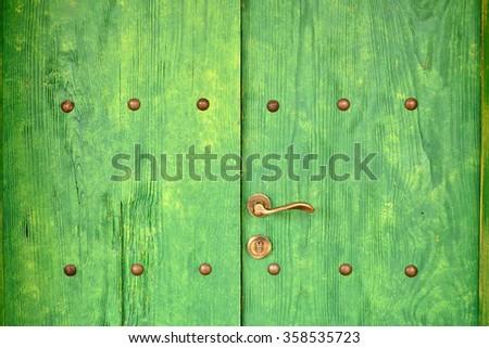 Antique green wooden doors with rivet and brass handles - stock photo