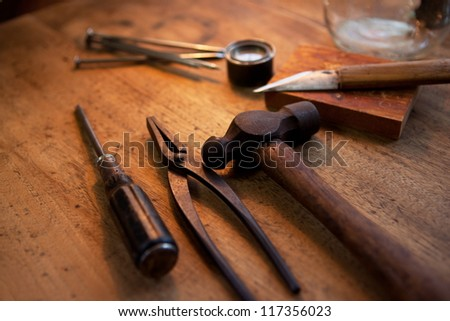 antique hammer, pliers and screw driver on a old wooden desk. With warm incandescent lighting. - stock photo