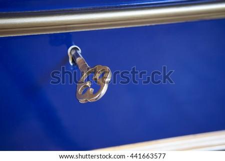 Antique key detail on a blue box background. Horizontal - stock photo