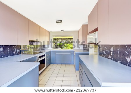 Antique Kitchen room with blue and pink storage combination, decorated back splash. Unique modern old home build in 1952. - stock photo