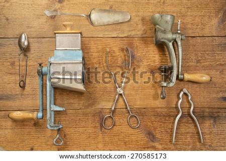 Antique kitchen utensils on a wooden background - stock photo