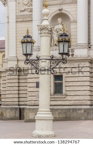Antique lamp post near Lviv State Academic Opera and Ballet Theatre. Theatre was built in classical tradition of Renaissance and Baroque architecture (Viennese neo-Renaissance style). Ukraine. - stock photo