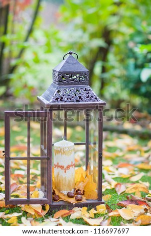 Antique lantern from the forged metal, with autumn leaves, candle and chestnuts - stock photo