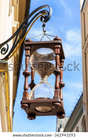 Antique large hourglass hanging in old town on blue sky background. Multicolored vibrant outdoors vertical image. - stock photo