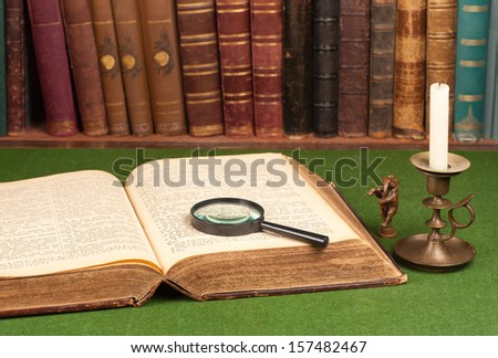 Antique leather books, tin candlestick and magnifying glass on green blotter. - stock photo
