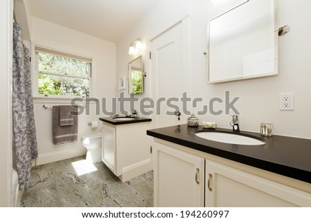 Antique luxury Bathroom in white with double sink and black granite counter tops. - stock photo