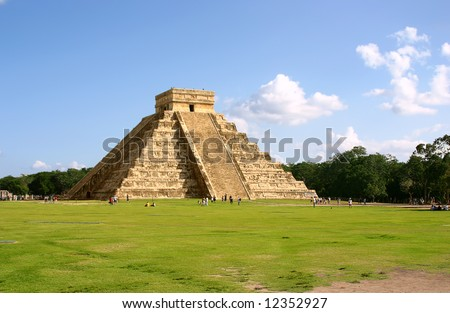 Antique mayan pyramid on green field over blue sky - stock photo