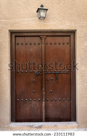 Antique old wooden door with metal bolt and lock - stock photo