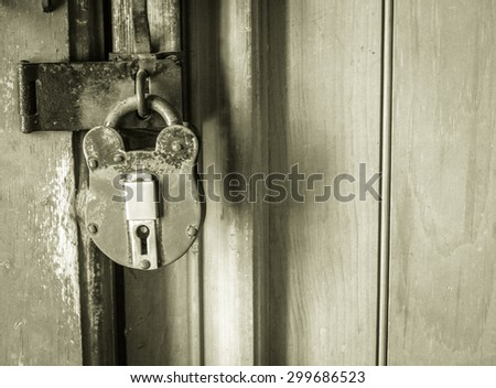 Antique Padlock. Antique padlock on a closed door in black and white. - stock photo
