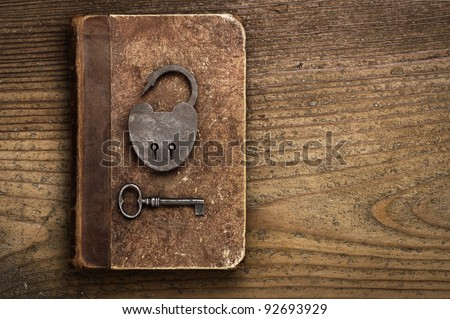 Antique Padlock with key on old book - stock photo