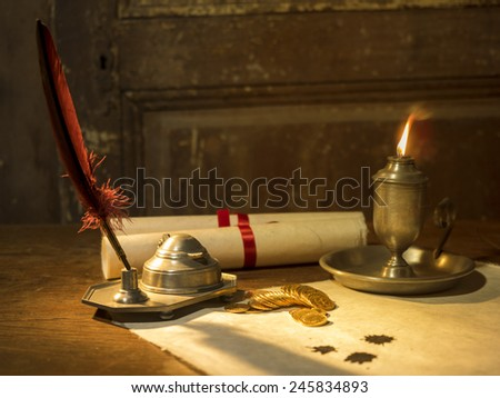 Antique parchment paper sheets lit by candlelight on a vintage colonial wood desk with ink writing feather quill, old candle light in candle-holder and gold coins - stock photo