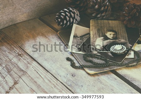antique photos and old book on wooden table. retro filtered image photo. selective focus  - stock photo