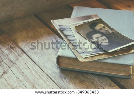 antique photos and old book on wooden table. retro filtered image. selective focus - stock photo