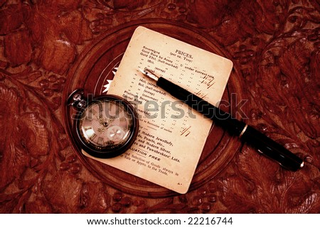 Antique pocket watch with pen on old paper and carved table top. - stock photo