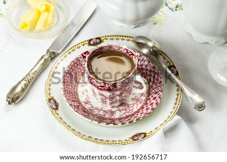 Antique porcelain breakfast setting with milk coffee on white cloth. Medium closeup of setting on table. - stock photo