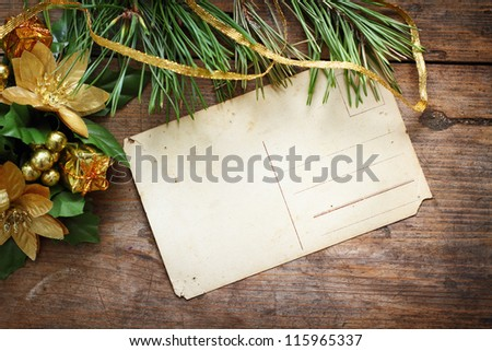 Antique postcard with christmas decorations on wooden background - stock photo