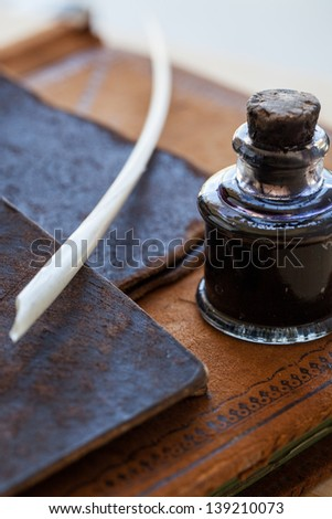 Antique quill pen and glass ink bottle with cork stopper on top of an antique leather bound ledger along with two leather antique small folders - stock photo