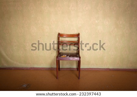 Antique ragged chair in old room interior with vintage wallpaper - stock photo