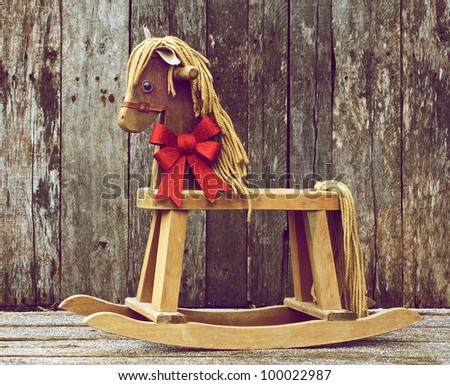 Antique rocking horse with a sparkling red Christmas bow around his neck on a rustic wooden backdrop. - stock photo