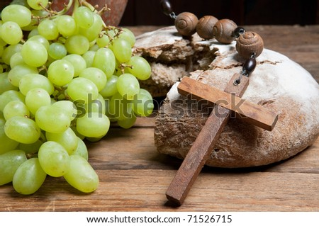 Antique rosary and rustic loaf of bread as christian symbols of faith - stock photo