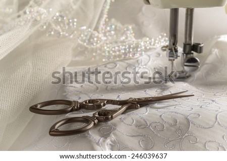 Antique scissors against wedding dress material and sewing machine - stock photo