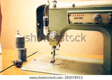 Antique sewing machine in work shop - stock photo