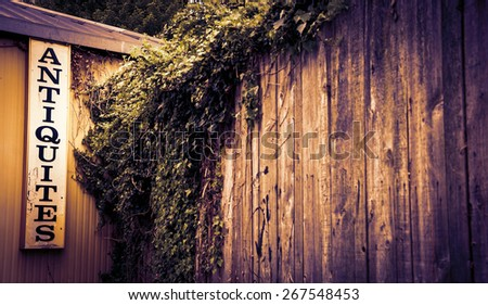 Antique shop sign near old wooden garden wall overgrown with a ivy shrub. Selective focus on the signboard. Toned photo. Vignette. - stock photo